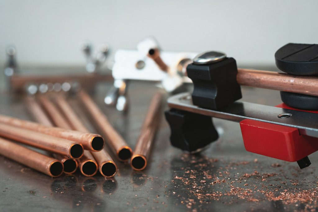 Brass pipes on a black workbench