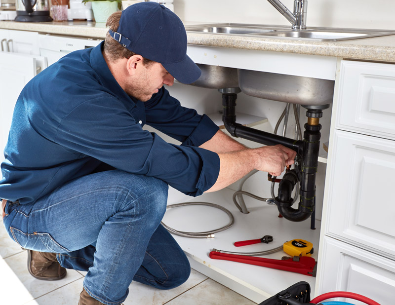 Plumber using a wrench on the pipes of a kitchen sink