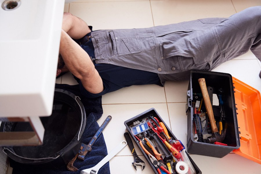 A plumber with an orange and black toolbox fixing a leaky pipe